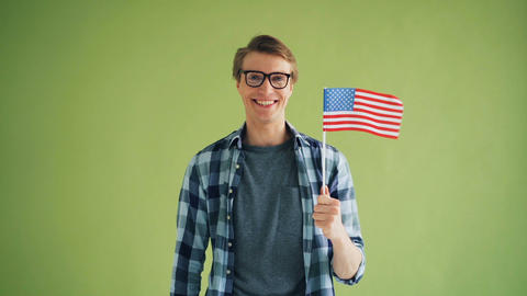 Portrait of American patriot holding flag of the USA smiling looking at camera Live Action