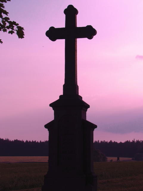 Silhouette of a cross on a background of sky with red clouds, evening twilight Photo