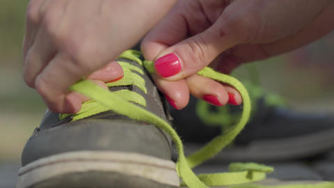 Womans hands tie shoelace of sneakers. Outdoor recreation Live Action
