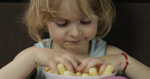 Girl sitting on sofa and eating corn puffs. Child smiling and taste puffcorns Footage