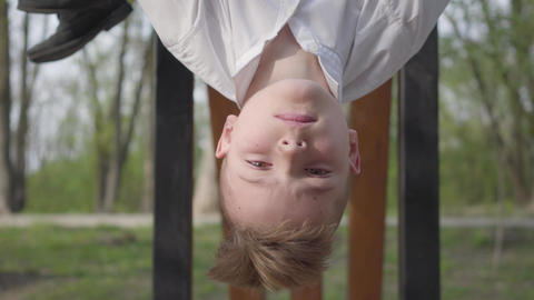 Teenager boy dangling his head down from the horizontal bar and smiling on the Live Action