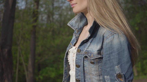 Beautiful woman with cellphone in long white skirt and jeans jacket walking Footage