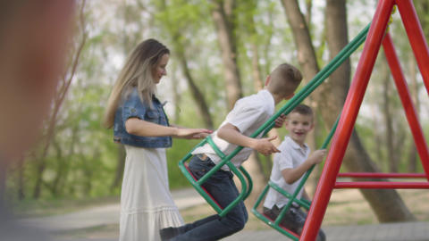 Happy mother pushing laughing two sons on swing in a park. Outdoor recreation Live Action