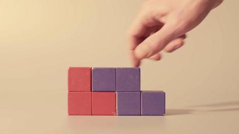 Mans hand picking 3D tetris Live Action
