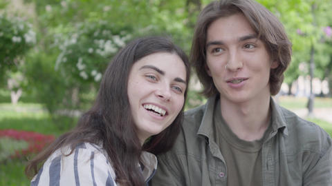 Portrait adorable young couple in casual clothes sitting at the bench talking Footage