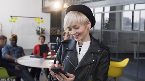 Attractive business woman working on the smartphone with group of young business Footage