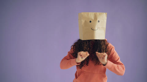 Girl with paper bag on head dancing showing thumbs-up showing like sign Footage