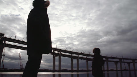 Two people silhouettes standing on river shore with highway bridge Live Action