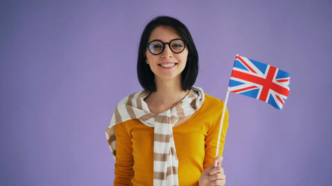 Slow motion of attractive British lady holding flag of Great Britain smiling Live Action