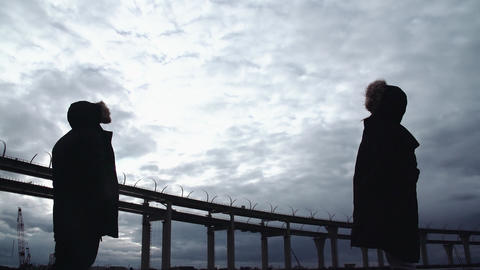 Two people silhouettes standing on river shore with highway bridge Footage