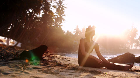 barefoot lady and dog silhouettes lit by morning sun Footage