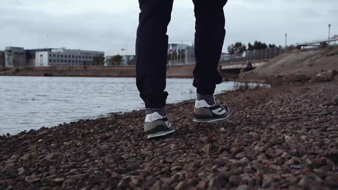 Legs of person in fashionable sneakers walking on rocky shore at urban area Footage