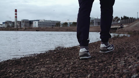 Legs of person in stylish sneakers walking on rocky shore at urban area Footage