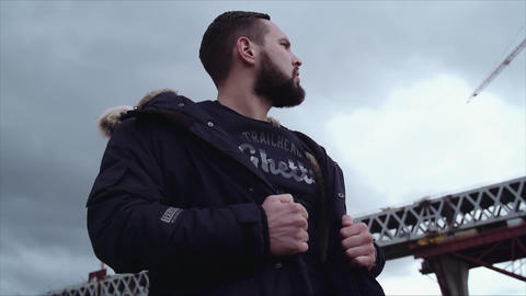 Well groomed bearded guy holding jacket on shoulders, looking around Live Action