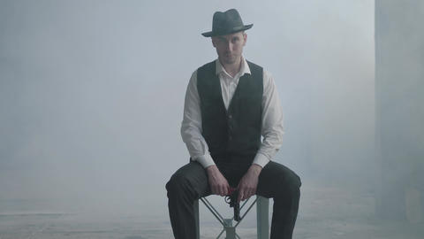 Handsome confident well-dressed man in a hat sitting on the chair holding a gun Footage