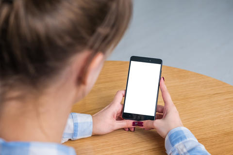 Woman holding black smartphone with white blank screen - mockup image Photo