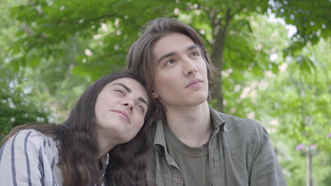 Portrait pretty young couple in love wearing casual clothes sitting at the bench Footage