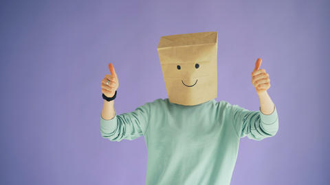 Person with paper bag on head showing thumbs-up gesture and moving body dancing Archivo