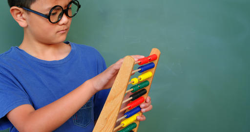 Front view of Asian schoolboy solving math problem with abacus in a classroom at school 4k Live Action