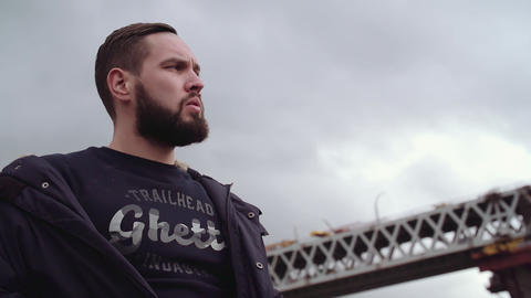 Bearded young guy holding jacket on shoulders, looking around Live Action