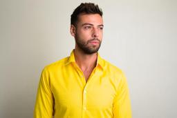 Studio shot of young handsome bearded businessman wearing yellow shirt Photo