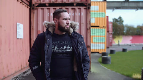 Well groomed bearded guy walks toward camera in winter jacket along cargo crates Live Action