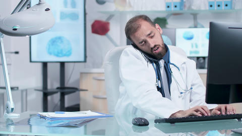 Doctor in his modern office talking on the phone GIF