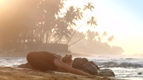 young pretty woman practices yoga against endless ocean Footage