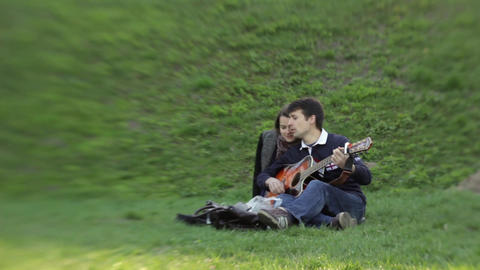 Two people in love are enjoying the sound of a guitar Live Action