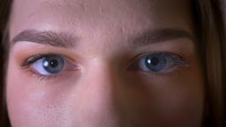 Closeup shoot of young brunette female face with eyes looking at camera and Footage