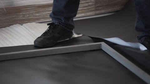 Man in black shoes and dark jeans stands on black sheet and grey metal frame Footage