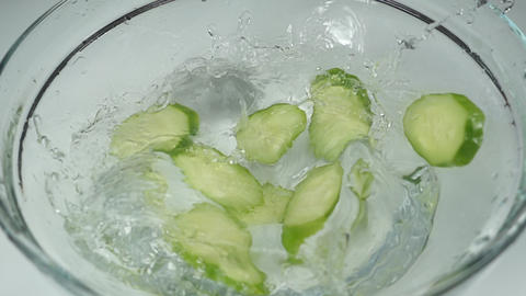Slow motion, several fresh cucumber slices falling into the water. Sliced green Live Action