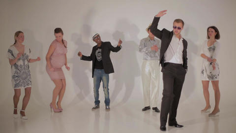 Three pretty women and three handsome interracial men dance in white studio Live Action