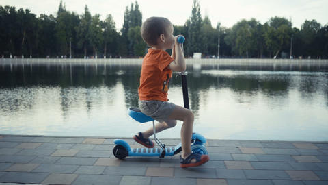 [alt video] Happy little boy two years old, riding a scooter in a...