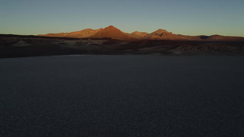 Aerial drone scene of white salar at sunset. Background of desertic eroded brown hills. Flying Footage