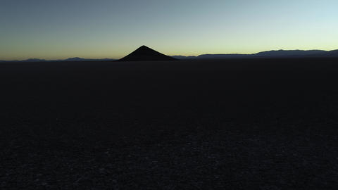 Aerial general view of silhuette of natural isolated pyamid in wide brown and white salar at sunset. Footage