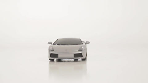 Silver color toy car is pushed by hand on white surface on white background Live Action