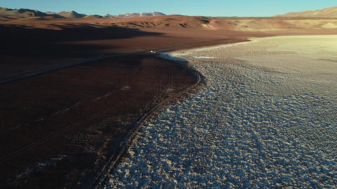 Aerial drone scene flying towars 4x4 off road van with caravan on limit of white salar with brown Footage