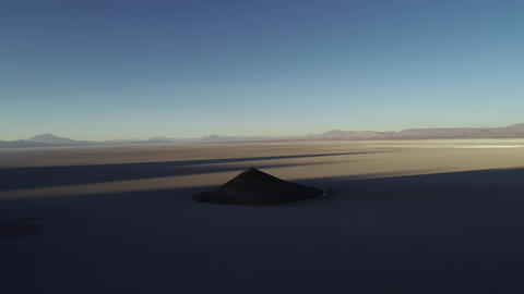 Aerial general view of natural isolated pyamid in wide brown and white salar at sunset, cone in Footage