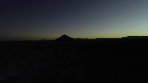Aerial drone scene of silhuette of mountains and natural perfect piramid at sunrise. Flying upwards. Footage