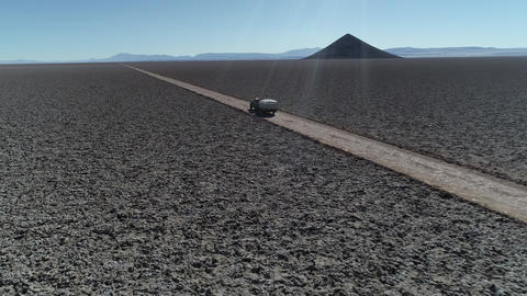 Aerial drone scene following 4x4 with caravan traveling off road on wide salar with natural pyramid Footage