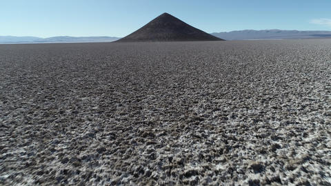 Aerial scene flying quickly along salar towards natural isolated pyamid in wide brown and white Footage