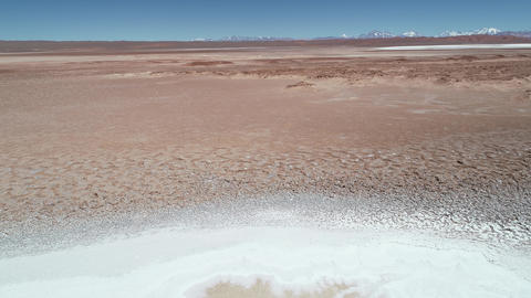 Aerial drone scene flying along blue lagoons with rocky shore at white salar. Ojos de mar, sea eyes, Footage