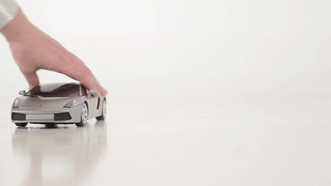 Grey plastic toy car is pushed by hand on white surface on white background Live Action