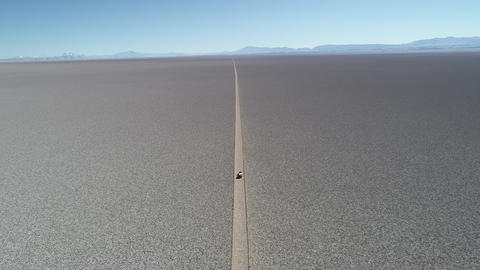 Aerial drone scene of 4x4 with caravan traveling along white wide salar with. From general view to Footage