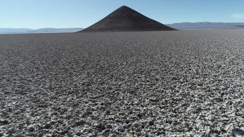 Aerial scene flying quickly ascending along salar towards natural isolated pyamid in wide brown and Footage