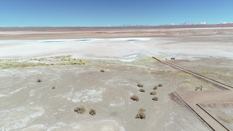 Aerial drone scene of wide white salar with circular blue lagoons, sea eyes, in Tolar Grande, Salta, Live Action