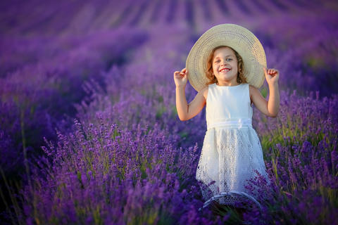Curly girl standing on a lavender field in white dress and hat with cute face Photo