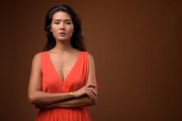 Studio shot of beautiful Asian woman against brown background Photo