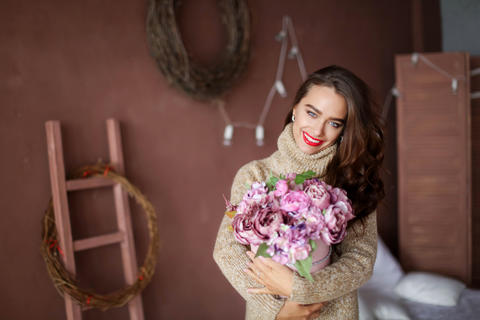 smiling woman in pajama holding gift box and looking at the camera, valentines Photo